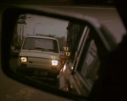 """""""a Short Film About Killing"""".  El auto blanco, visto desde el la perspectiva del taxista con las luces  de frente encendidas, ubicado frente a él. Los faros se prenderán y apagarán varias veces, antes de que el taxista inicie el recorrido que su cliente y asesino, Jacek, le señale."""