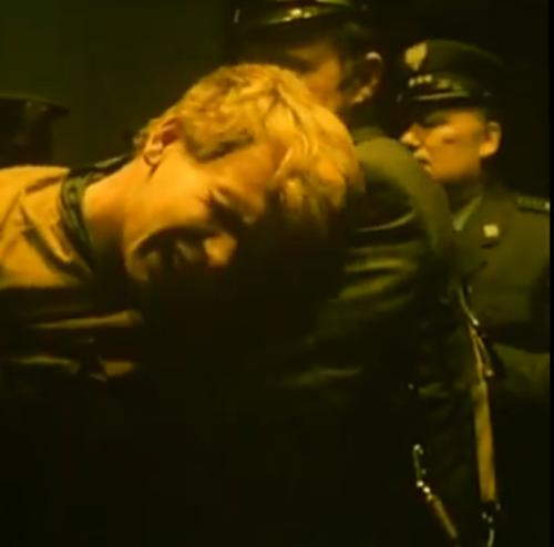 """""""Decálogo Cinco: No Matarás"""".  Jareck también se arroja al piso e intenta soltarse, pero los guardias lo inmovilizan más rápidamente y no lo dejan mirar al piso. Un guardia ordena, entonces,  que se ejecute la sentencia."""