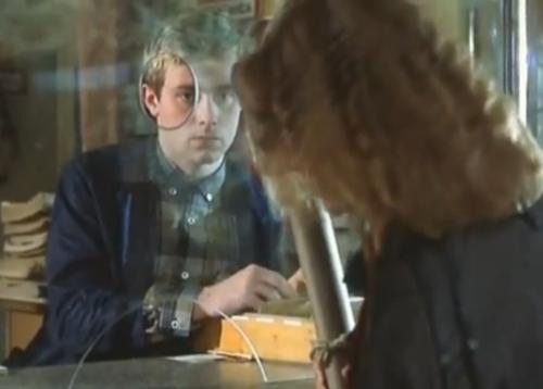 """""""A Short Film About Love"""". Tomek observa desde la ventanilla de su puesto a Magda, mientras ella se acomoda el zapato. Este detalle no aparece en """"Decálogo Seis""""."""