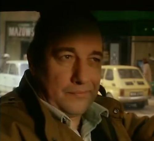 """""""A short Film About Killing"""". El taxista sonríe irónicamente al asistir al festejo público de Piotr por haberse recibido de abogado, mientras espera frente al semáforo."""