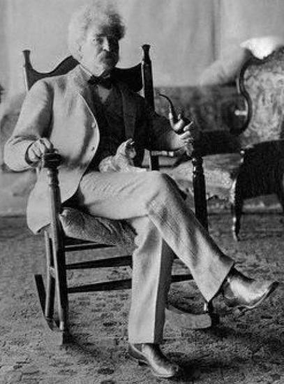 """Mark Twain, el autor de """"Tom Sawyer"""" y """"El Diario de adán y Eva"""" con un pequeño gato sobre las piernas."""