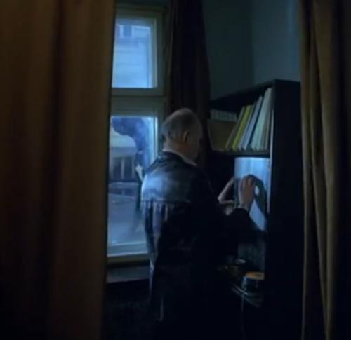 Primera aparición del perro negro, que se distingue detrás de la ventana del negocio.